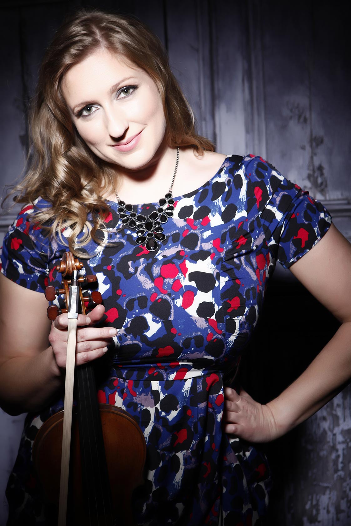 Seonaid Aitken posing with violin in colourful dress