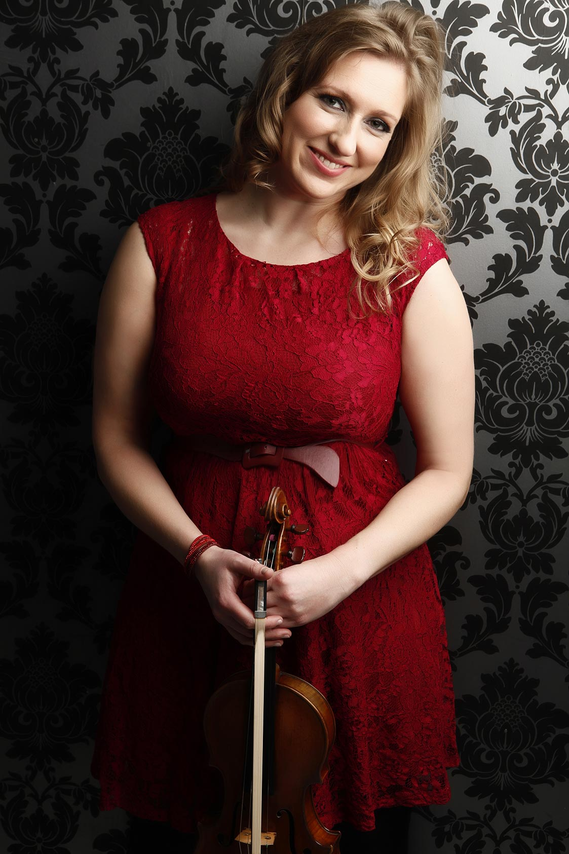 Seonaid Aitken posing with violin in red dress